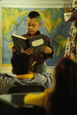 boy reading from a book in a classroom