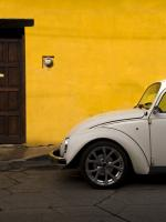 Volkswagen Beetle parked in front of a yellow building.