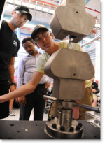 students_using_machine_with_teacher